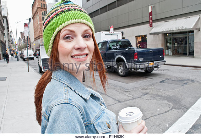 Candid portrait of young woman with takeaway coffee - Stock Image
