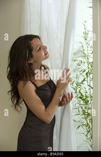 Young woman moving curtain to look out window - Stock Image