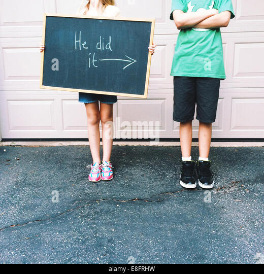 Girl (8-9) and boy (12-13) with blackboard sign - Stock Image