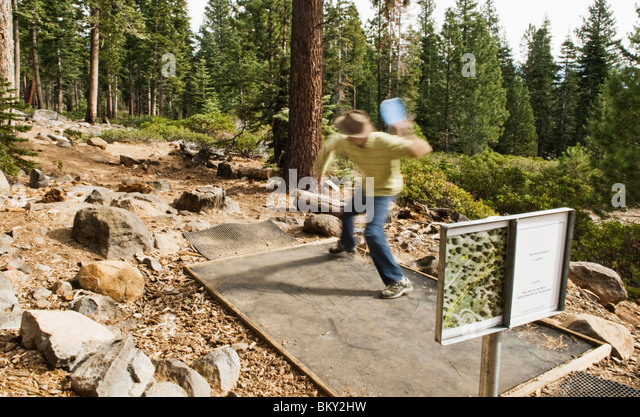 A young man tees off with a distance driver during a game of disc golf in Lake Tahoe, California. - Stock Image