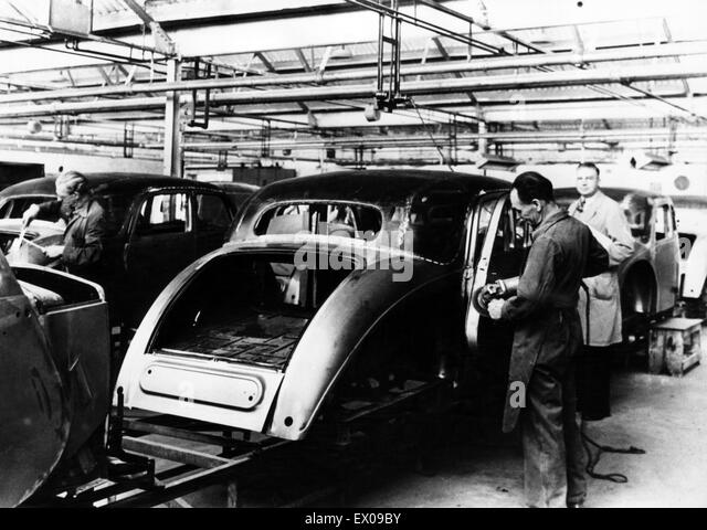 Production of Riley saloons in the late 1940s. Skilled tradesmen are seen fettling and finishing the bodies on the - Stock Image