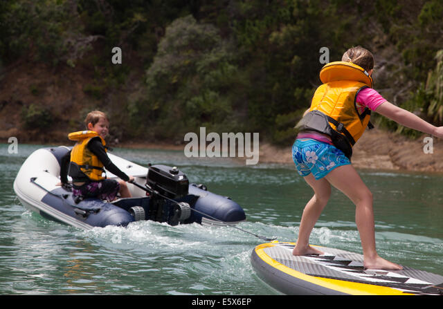Brother in motor dinghy towing sister standing on paddleboard - Stock Image