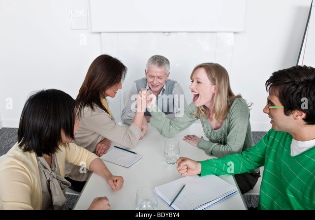 arm wrestling in group meeting - Stock Image