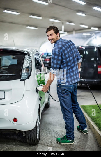 Full length portrait of young man charging electric car at gas station - Stock Image