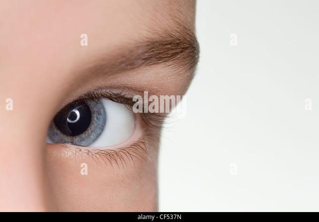 left blue eye of child close up isolated on white background - Stock Image