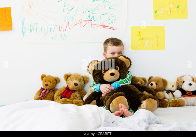 Boy hugging teddy bear on bed - Stock Image