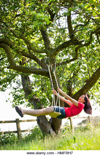 Happy woman swinging on tree swing in sunny rural summer yard, carefree, playful, fun - Stock-Bilder