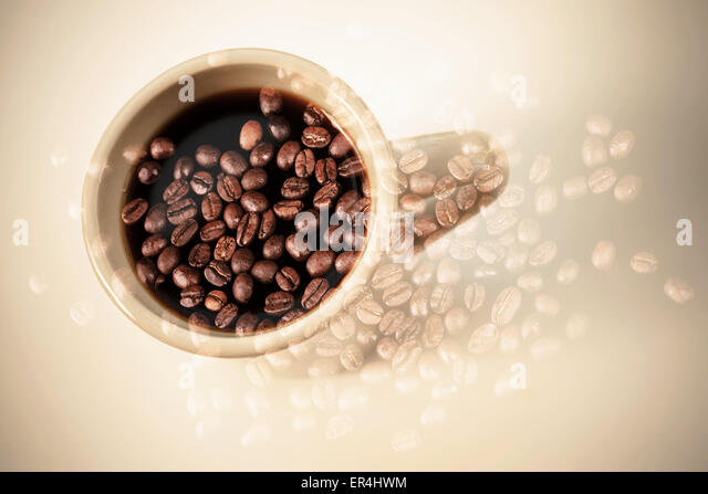 White coffee cup stand on a table over dark rusted coffee beans texture. Double exposure photo with vintage style - Stock Image