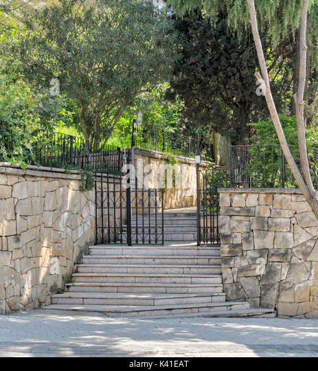 Ascending marble stairs leading to a public park, Stone wall, and fence iron door, Buyukada Island, Istanbul, Turkey - Stock Image