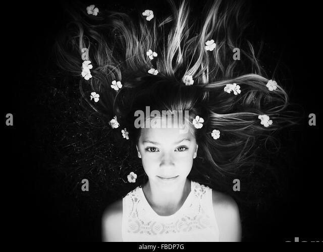 Portrait Of Girl Lying Down With Flowers In Hair - Stock-Bilder