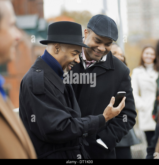 Two men standing side by side keeping in contact using mobile phones and checking the screen laughing - Stock Image