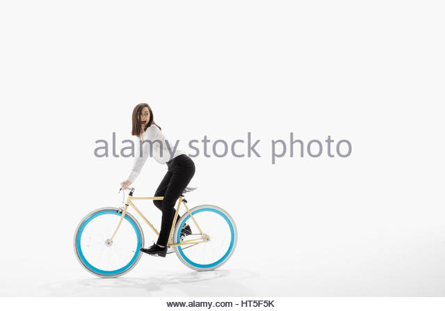 Playful businesswoman riding bicycle against white background - Stock-Bilder