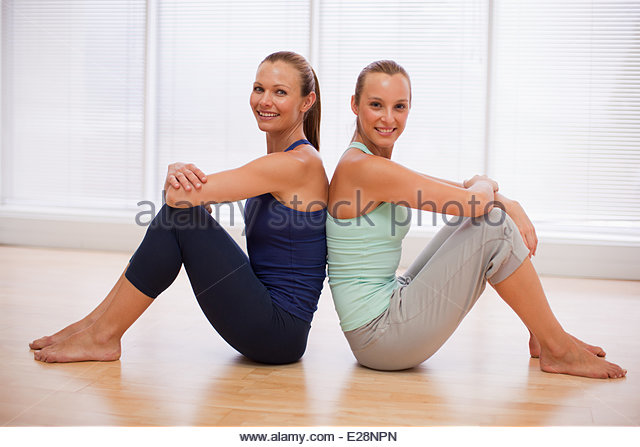 Portrait of smiling women sitting back to back in fitness studio - Stock Image