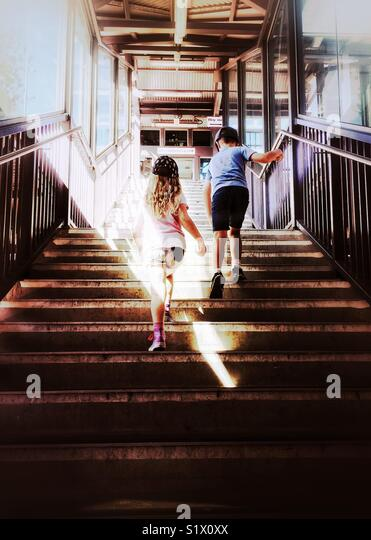 Two kids climb stairs at railway station. Young boy and girl walk up stairway through sunbeam - Kiama, NSW, Australia - Stock Image