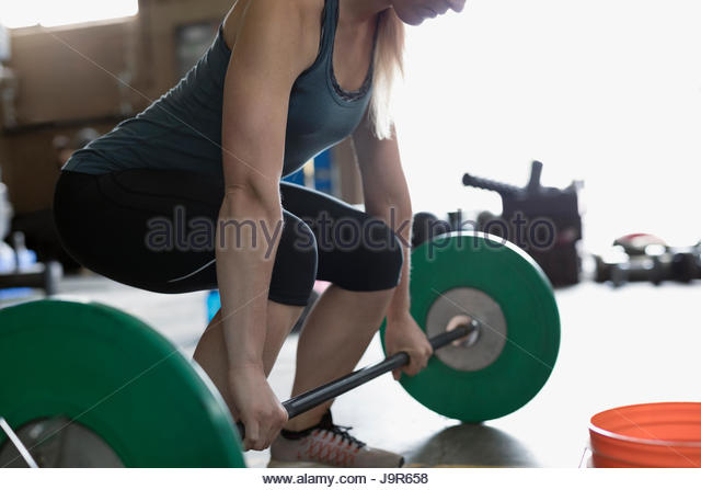 Strong woman weightlifting, doing barbell deadlift at gym - Stock Image
