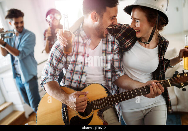 Cheerful young friends having party together and playing instruments - Stock Image
