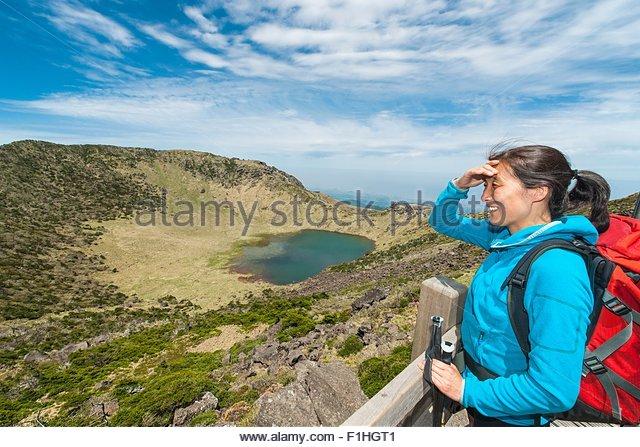 Hiker enjoying the view at the top of Hallasan, the highest mountain in Korea, Jeju Island, South Korea - Stock Image
