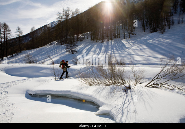 Man snowshoeing, carrying child in baby carrier - Stock Image