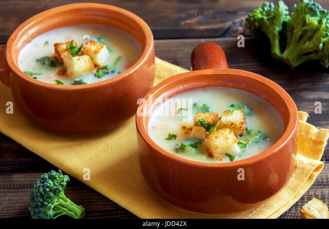 Vegetable and cheddar cheese cream soup with broccoli and croutons over wooden background with copy space - homemade - Stock Image