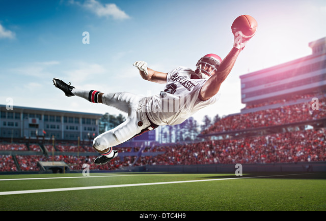 American football player catching ball mid air in stadium - Stock Image