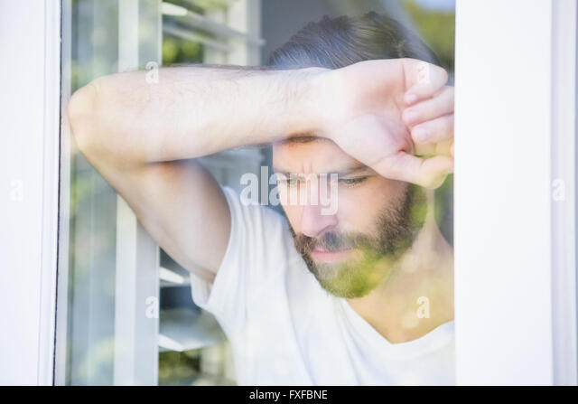 Depressed man leaning his head on window glass - Stock Image