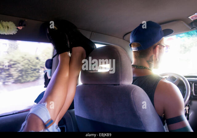 Young man driving car whilst girlfriend has feet up in back seat - Stock Image