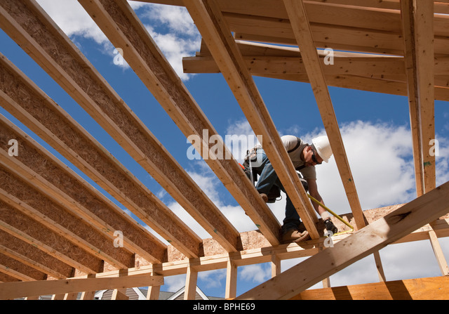 Carpenter working on second floor of a house - Stock Image