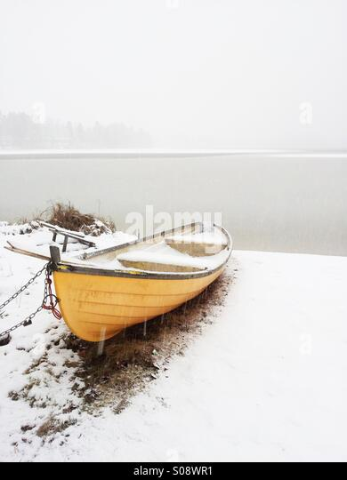 A rowboat covered in snow, photographed during a snowstorm at Lake Palokkajärvi in Jyväskylä, Finland. - Stock Image