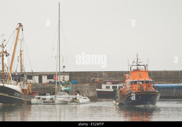 Newlyn Harbour, Cornwall, UK. 18th July, 2014. The Penlee RNLI Lifeboat tows a 30 foot Trimaran into Newlyn Harbour - Stock Image