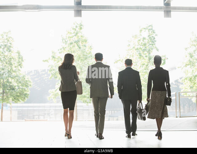 Corporate business people walking in a row - Stock Image