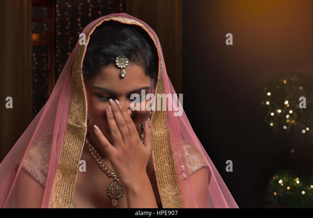 Woman in bridal dress laughing while feeling shy - Stock Image