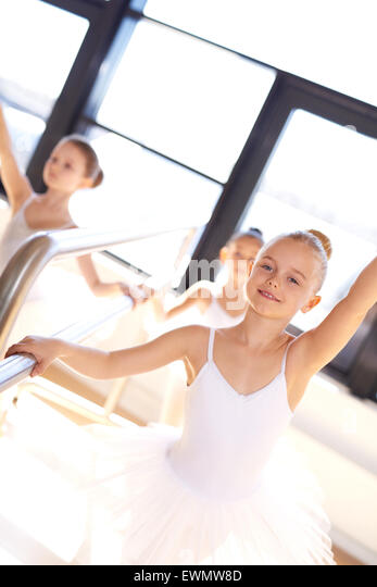 Pretty smiling young ballerina in training using the bar in the ballet school studio to practice her positions and - Stock Image