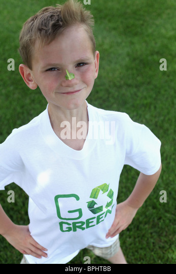 smiling young boy standing  & wearing with 'go green 'tee shirt - Stock-Bilder