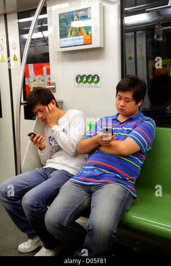 China Shanghai Metro subway public transportation riders Asian man Green Line 2 using smartphone texting - Stock Image