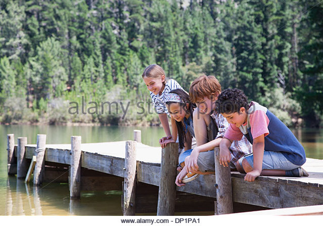 Kids sitting on dock - Stock Image