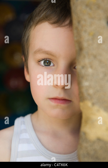 Little boy behind tree trunk, portrait - Stock Image