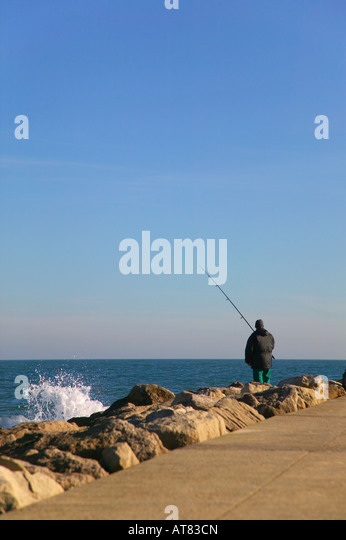 An angler line fishing from some rocks - Stock Image