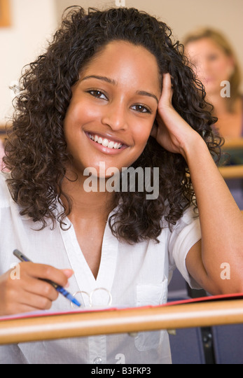 Student in class taking notes (selective focus) - Stock Image