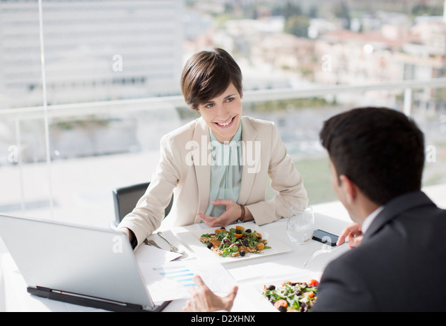 Businessman and businesswoman with laptop meeting over lunch - Stock Image