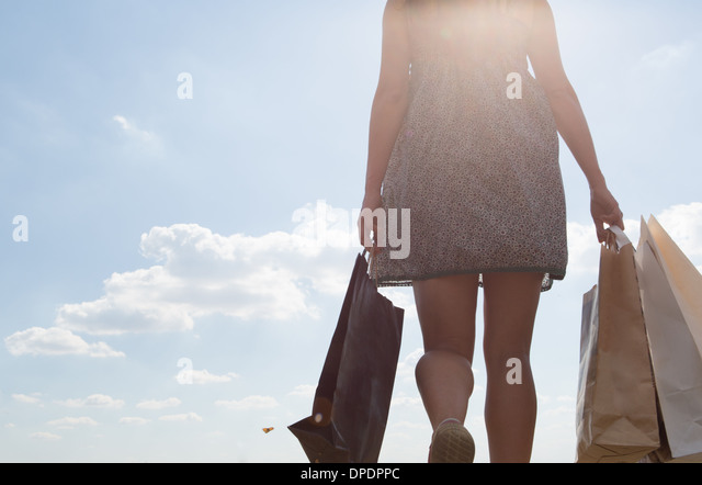 Mid section of woman carrying shopping bags - Stock Image