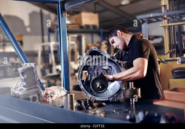 Mechanic fixing part in auto repair shop - Stock Image