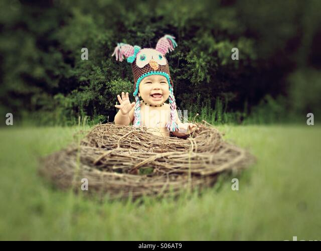 Baby girl in an owl hat sitting in a nest as part of a themed photo shoot. - Stock Image