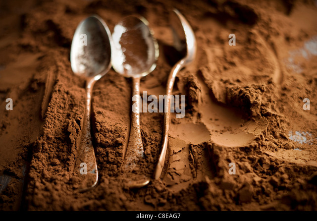Spoons and chocolate powder - Stock Image