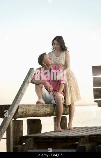 Mature couple looking at each other and smiling on pier, Bavaria, Germany - Stock-Bilder