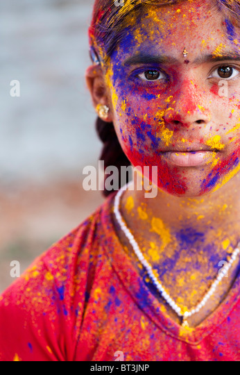 Young Indian girl covered in coloured powder pigment - Stock Image