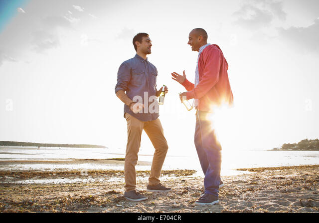 Men drinking beer and chatting on beach - Stock Image