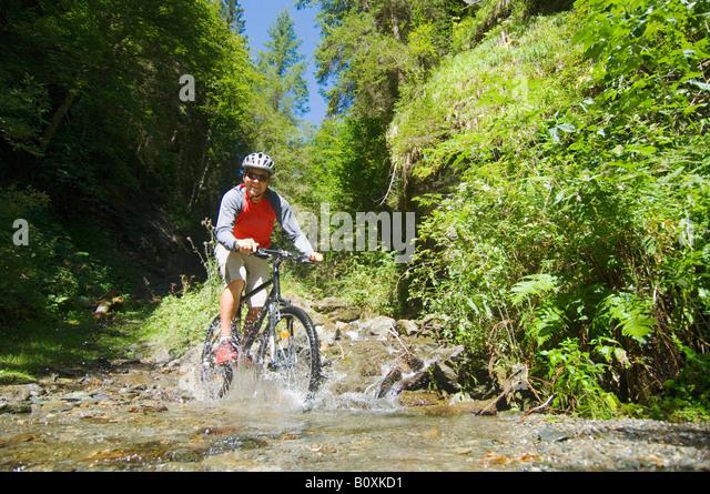 Mountainbiker crossing brook - Stock Image