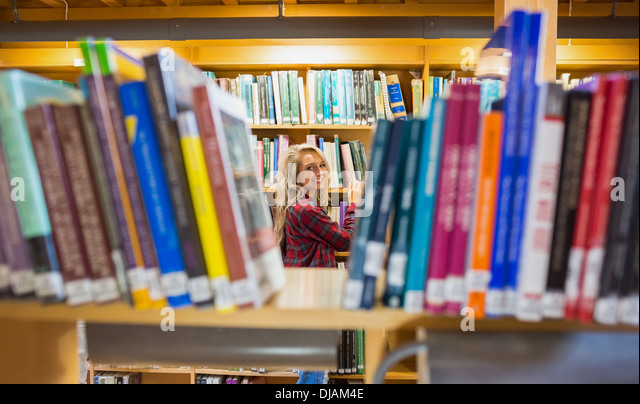 Smiling female amid bookshelves in the library - Stock Image