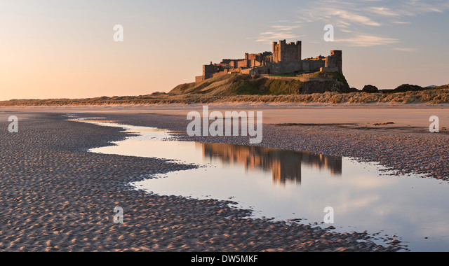 Bamburgh Castle and reflection in Bamburgh Beach tidal pools, Northumberland, England. Spring (April) 2013. - Stock-Bilder