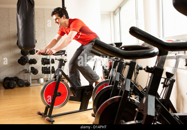 Man using stationary bicycle at gym - Stock Image